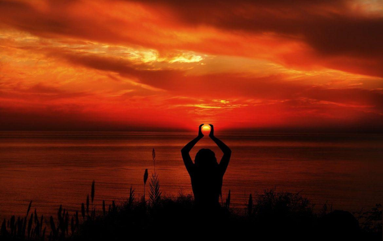 Frau im im Abendrot am Meer die Sonne in ihren Händen