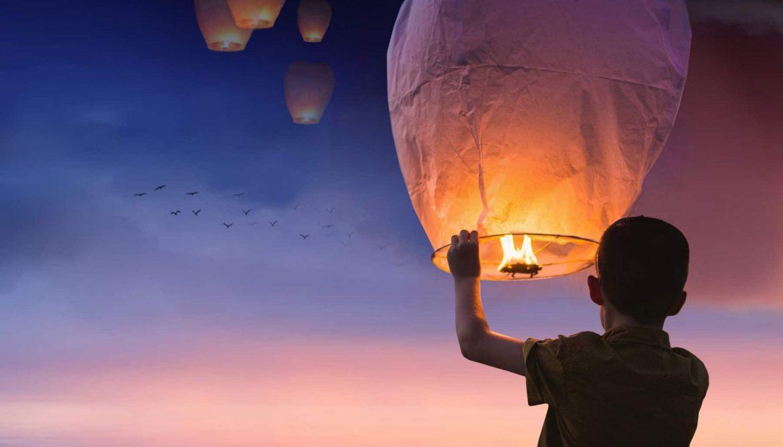 Kind mit Feuer unter Ballon der fliegen wird