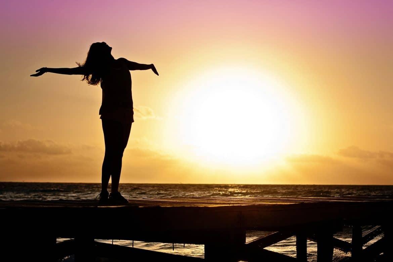 Frau am Meer mit offenen Armen zum Himmel im Sonnenuntergang