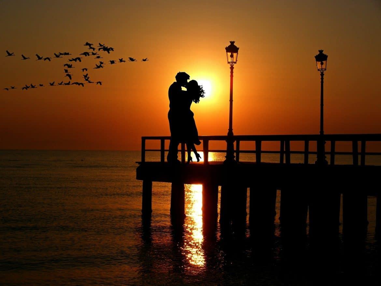 Liebespaar im Mai Sonnenuntergang auf einem Steg im Meer