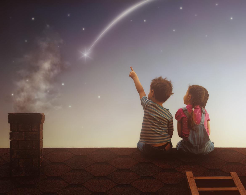 kleiner Junge und Mädchen auf dem Dach sitzend, einer Sternschnuppe nachschauend