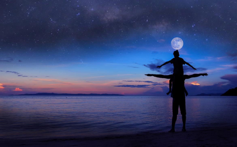 Silhouette von Vater mit Tochter auf den Schultern und dem Mond oben drüber